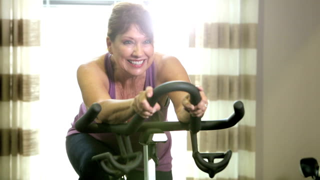 Senior women in gym on exercise bike