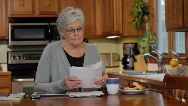 ms senior women in kitchen looking at bills / albany,  new york, united states  - physical pressure stock videos & royalty-free footage