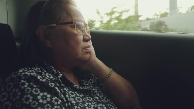 vidéos et rushes de femme âgée dans la voiture au coucher du soleil - passager
