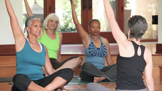 senior women in yoga class - leisure activity stock videos & royalty-free footage
