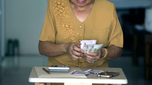 vídeos de stock e filmes b-roll de senior women is counting money - encontrar