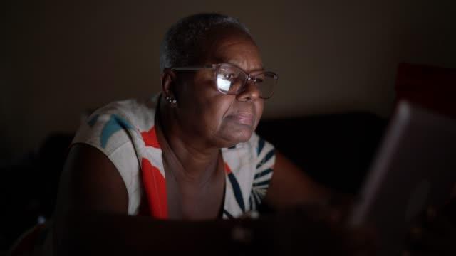senior women lying down on sofa using digital tablet - dark stock videos & royalty-free footage