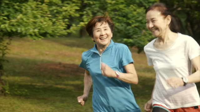 senior women running in yoyogi park - senior adult stock videos & royalty-free footage