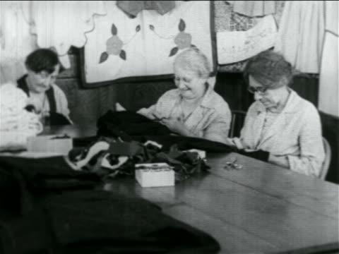b/w 1934 3 senior women sewing in wpa garment factory / documentary - 雇用促進局点の映像素材/bロール