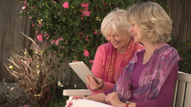 vídeos de stock, filmes e b-roll de ms senior women sharing digital tablet outdoors - idoso na internet