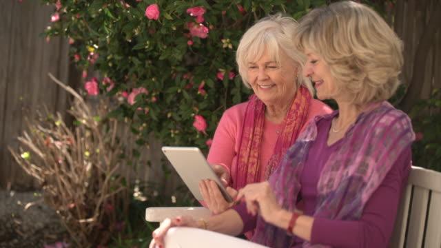 vídeos de stock, filmes e b-roll de senior women sharing digital tablet - idoso na internet