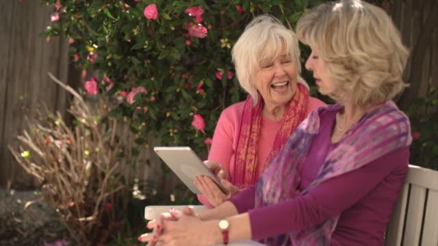 vidéos et rushes de ms senior women sharing digital tablet - seniornaute