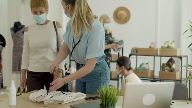 vídeos de stock e filmes b-roll de senior women shopping in fashion store during coronavirus pandemic - viciado em compras