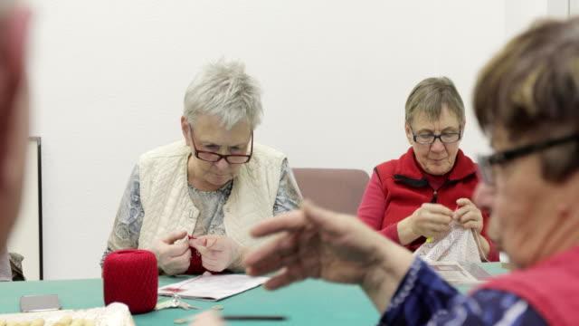 vídeos de stock, filmes e b-roll de mulheres idosas socializando e tricotando ou tecelagem - tecer