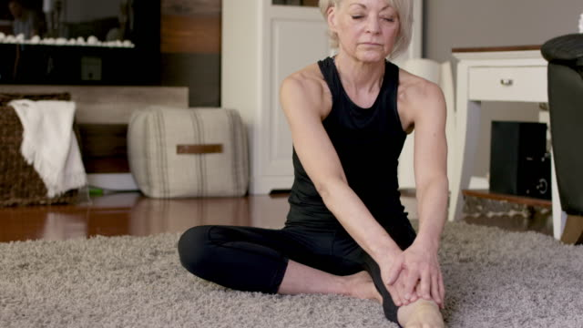 a senior women stretches at home. - stretching stock videos & royalty-free footage