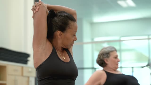 senior women stretching in fitness class - 60 69 years stock videos & royalty-free footage
