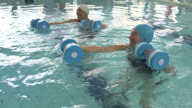 stockvideo's en b-roll-footage met senior women taking part in an aqua aerobics class in an indoor swimming pool - binnenbad
