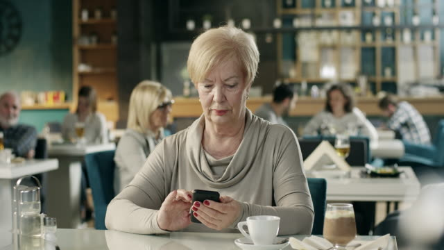 senior women texting in restaurant - one senior woman only stock videos & royalty-free footage