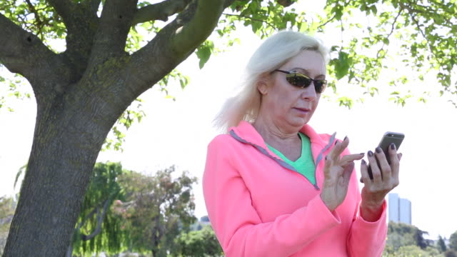 A senior women using a cellular device outdoors in a park.