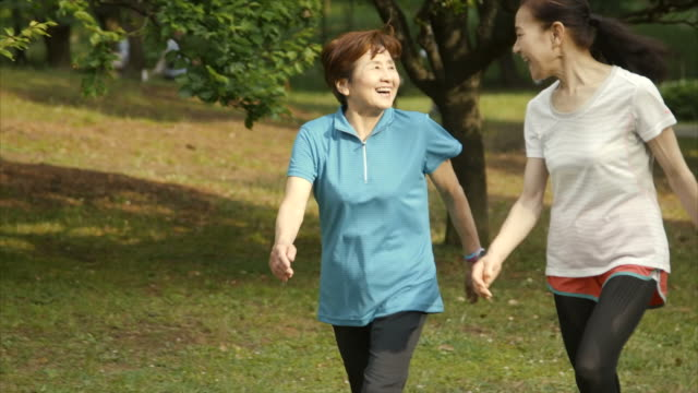 senior women walking in yoyogi park - natural parkland stock videos & royalty-free footage