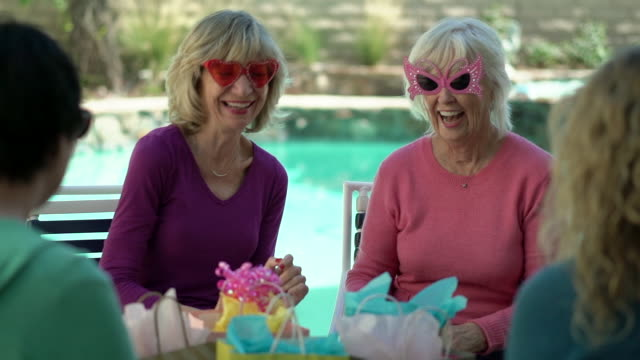 MS Senior women wearing funning sunglasses by swimming pool