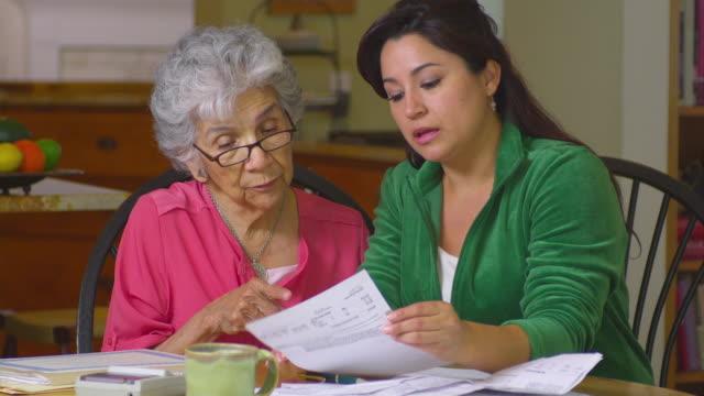 vídeos de stock e filmes b-roll de ms senior women with adult daughter doing paperwork, austin, texas, usa - financial bill