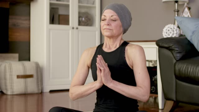a senior women with cancer does yoga at home. - survival stock videos & royalty-free footage