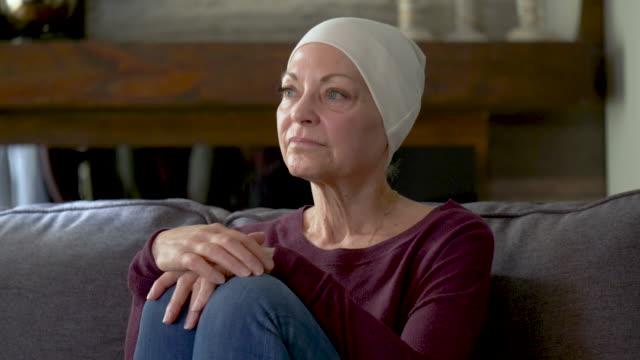 vídeos de stock, filmes e b-roll de uma mulher sênior com cancro está sentando-se no sofá. - radioterapia