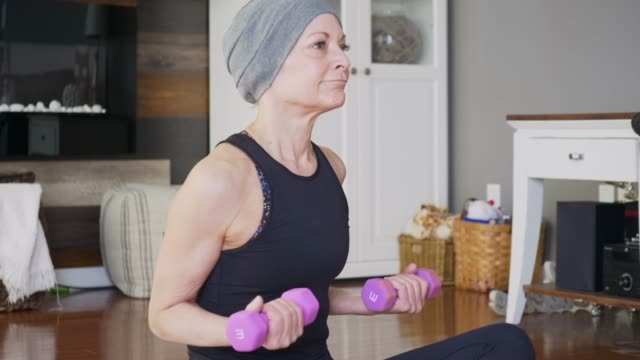 a senior women with cancer works out at home. - arm curl stock videos & royalty-free footage