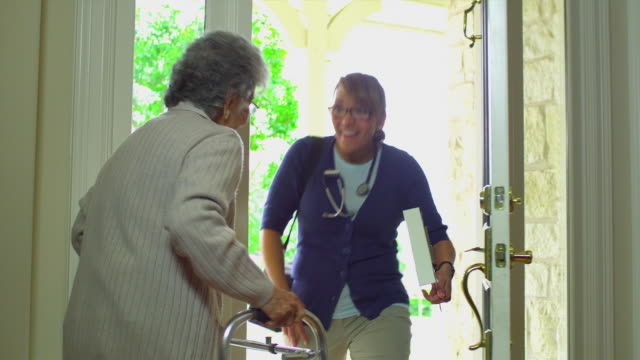 ms senior women with walker greeting health care worker at door, austin, texas, usa - social worker stock videos & royalty-free footage