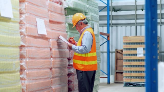 Senior workers in a warehouse or factory are going about their business and preparing goods for delivery.