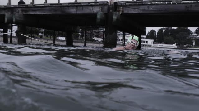 vídeos y material grabado en eventos de stock de senior worman swimmer begins swim in cold grey waters of san francisco bay. - gorro de baño
