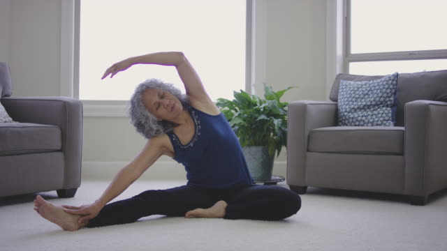 Senior-Age Adult Ethnic Female Doing Yoga in Living Room