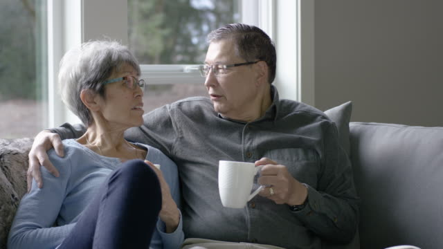 Senior-Age Ethnic Couple Sitting on Couch While Enjoying Their Morning Drink