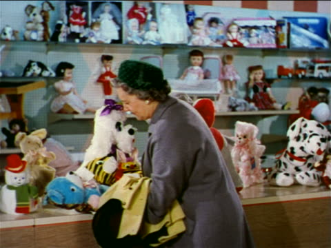 1962 senior/middle aged woman looking at stuffed animals in toy store / industrial - toy store stock videos and b-roll footage