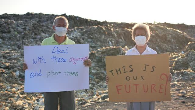 vídeos de stock, filmes e b-roll de idosos estão fazendo campanha sobre o futuro da pilha de lixo global. - poluição do plástico