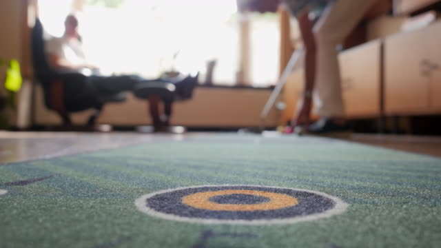 stockvideo's en b-roll-footage met seniors at home: practicing golf putts indoors - huis interieur