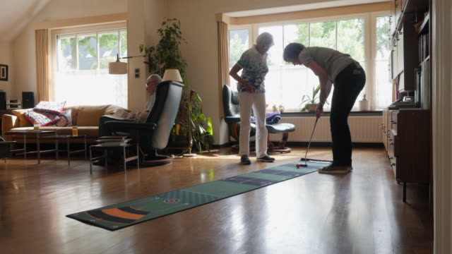 seniors at home: practicing golf putts indoors - links golf stock videos & royalty-free footage