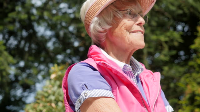 seniors at home: practicing golf swings in her garden - sun visor stock videos & royalty-free footage