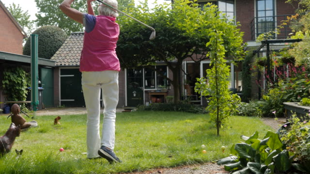 vídeos y material grabado en eventos de stock de seniors at home: practicing golf swings in her garden - 80 89 años