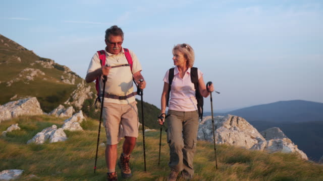 seniors couple hiking on a mountain - hill stock videos & royalty-free footage