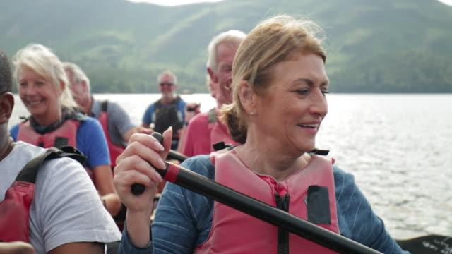 vidéos et rushes de aînés appréciant et ayant l'amusement dans le bateau d'aviron - tourisme