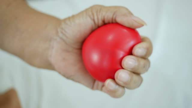 senior's hand exercise  with red heart ball