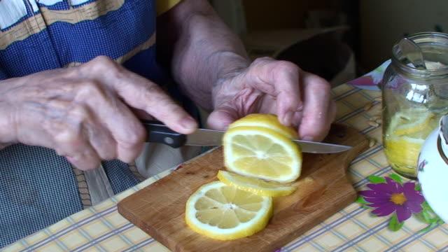 vídeos y material grabado en eventos de stock de senior's hands cutting limón - vena humana