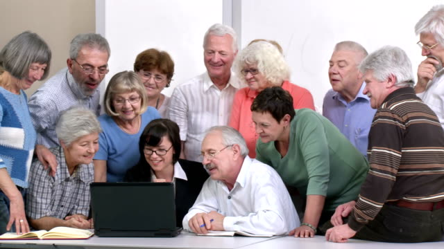 hd: seniors having fun while taking computer lessons - 55 59 år bildbanksvideor och videomaterial från bakom kulisserna
