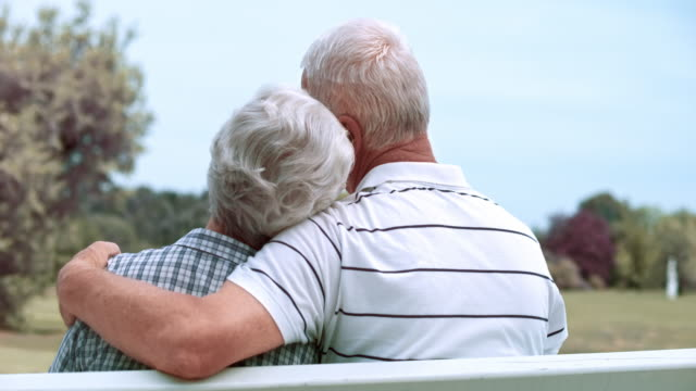 slo mo ds seniors in love sitting on park bench - senior couple stock videos & royalty-free footage