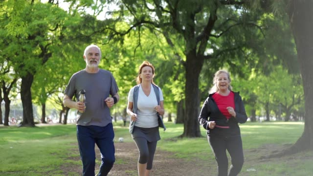 seniors jogging in park - active lifestyle stock videos & royalty-free footage