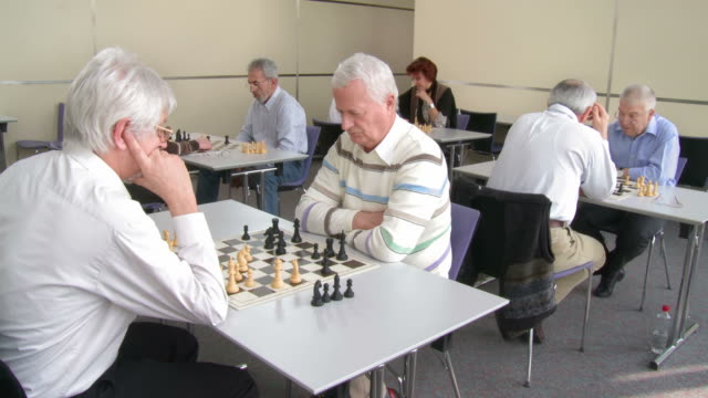 hd: seniors playing chess in community center - community centre stock videos & royalty-free footage
