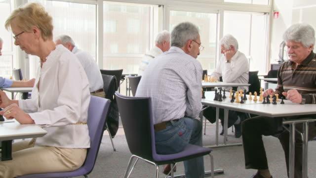 vidéos et rushes de hd dolly: personnes âgées jouant aux échecs - centre culturel
