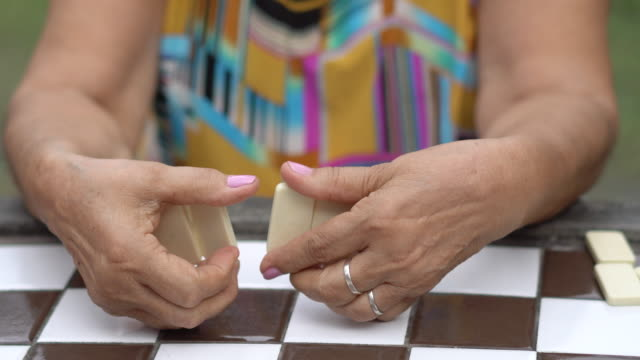 seniors playing domino in the public park - 70 79 years stock videos & royalty-free footage