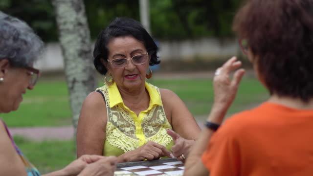 stockvideo's en b-roll-footage met senioren spelen domino in het openbare park - arts culture and entertainment