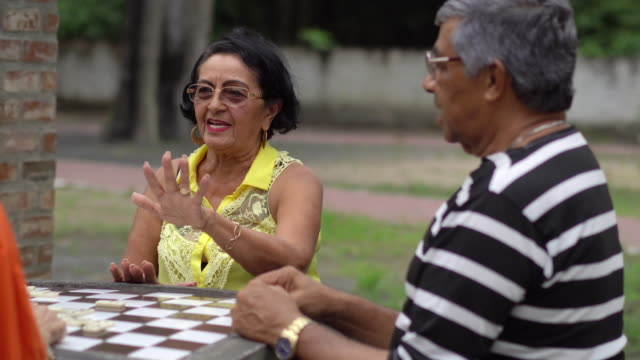 seniors playing domino in the public park - 70 79 years stock videos and b-roll footage