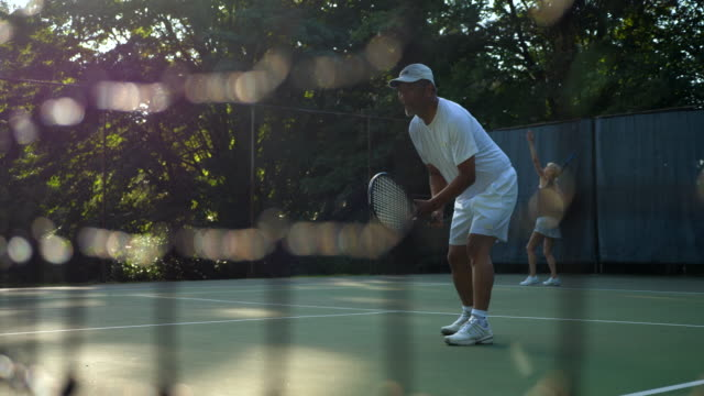 ms seniors playing mixed doubles tennis match on summer morning - patience stock videos & royalty-free footage