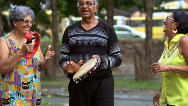 seniors playing the tambourine, singing and dancing in the public park - 70 79 years stock videos and b-roll footage
