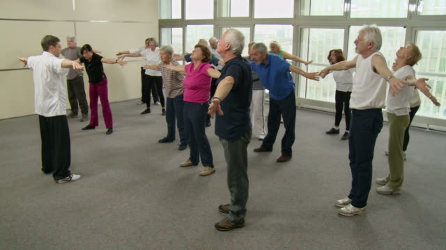 hd: seniors practicing tai chi relaxation exercises - community center stock videos and b-roll footage